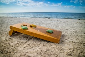 Photo of corn hole board on beach.